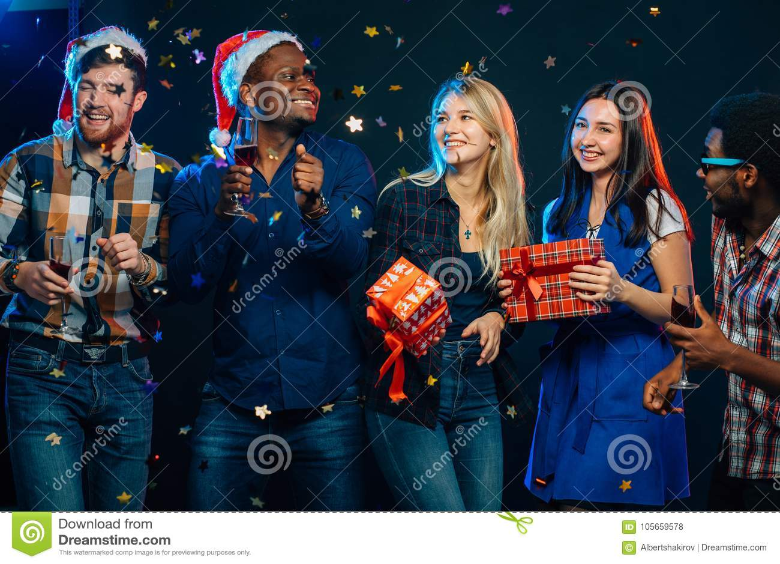 一起庆祝新年 小组圣诞老人帽子的美丽的青年人