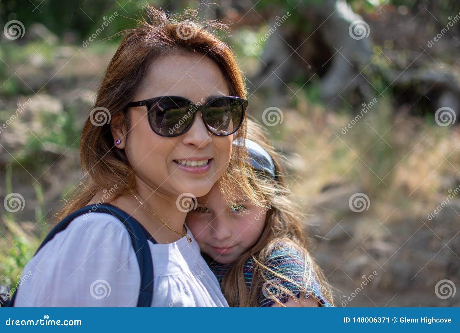 一起微笑,当站立在森林前面在公园时的拉提纳妇女和女儿