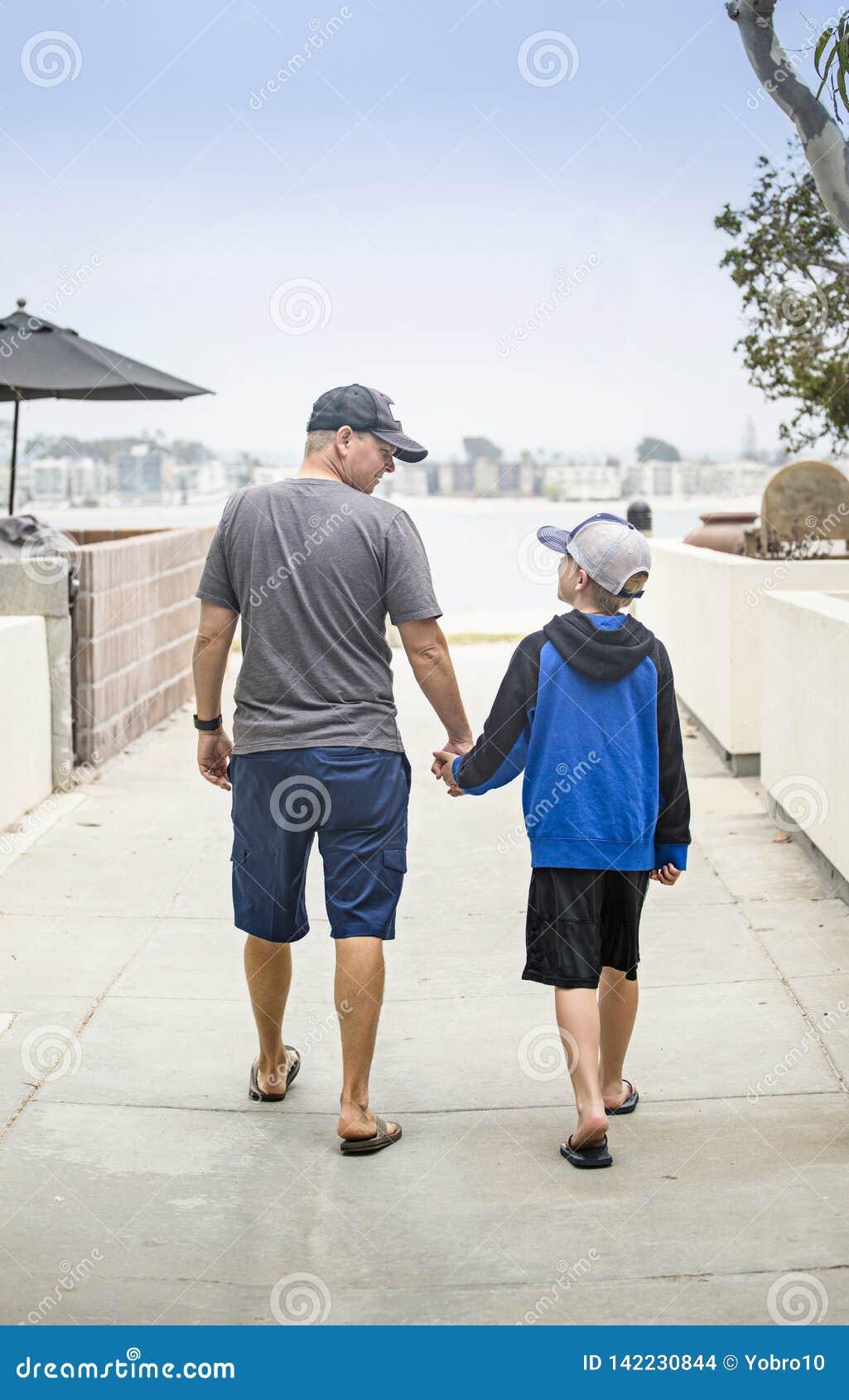 一起手拉手走在边路的父亲和儿子