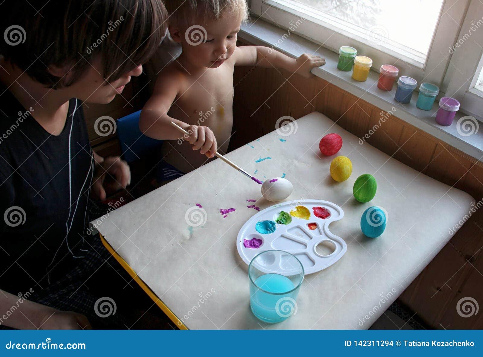 一起洗染复活节彩蛋的母亲和她的小孩白肤金发的儿子在家