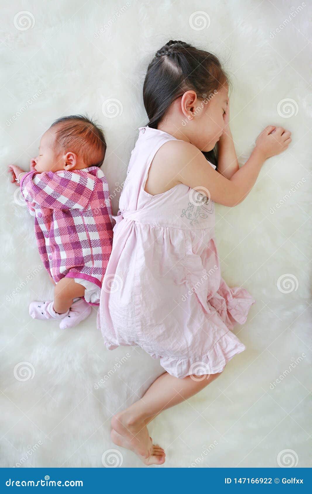 一起睡觉在白色毛皮背景的亚裔姐姐和新生儿男孩