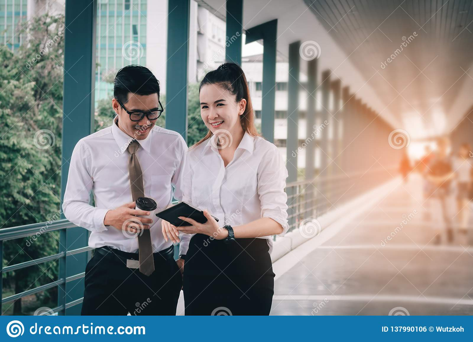 一起研究数字片剂和分析图报告的商人在公司建筑物的走道