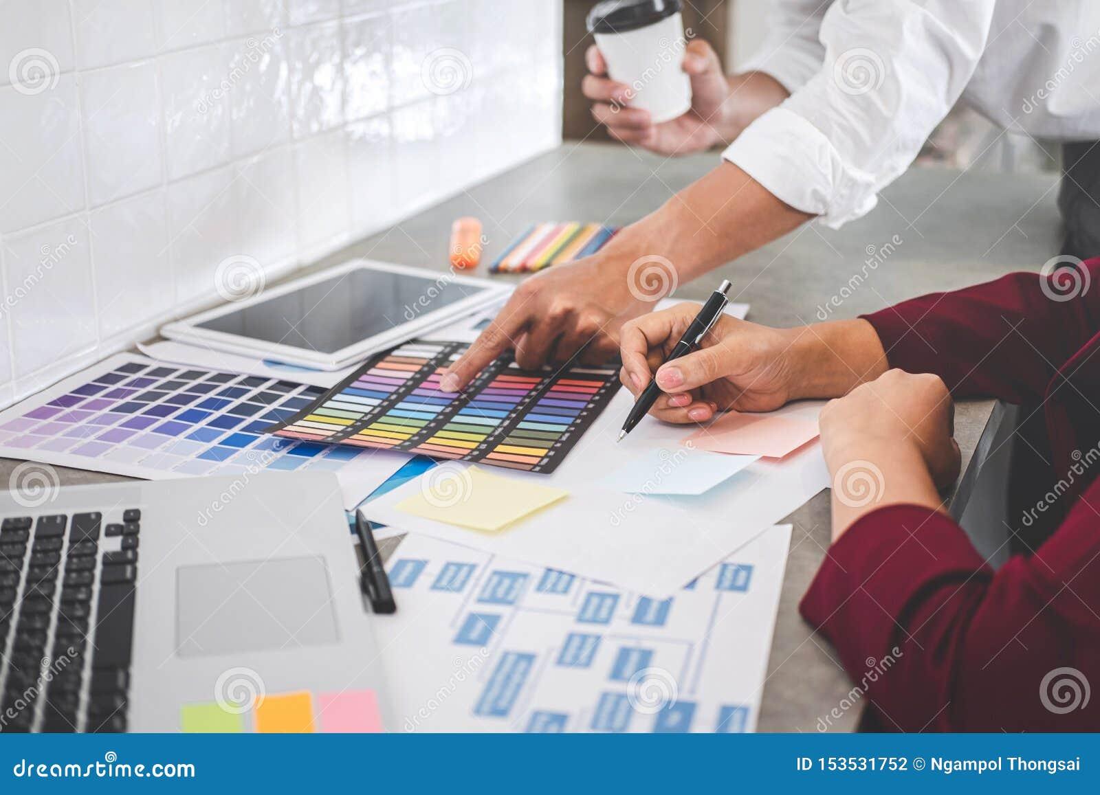 一起研究项目的年轻创造性的设计师配合和选择颜色选择着色的样片样品在数字