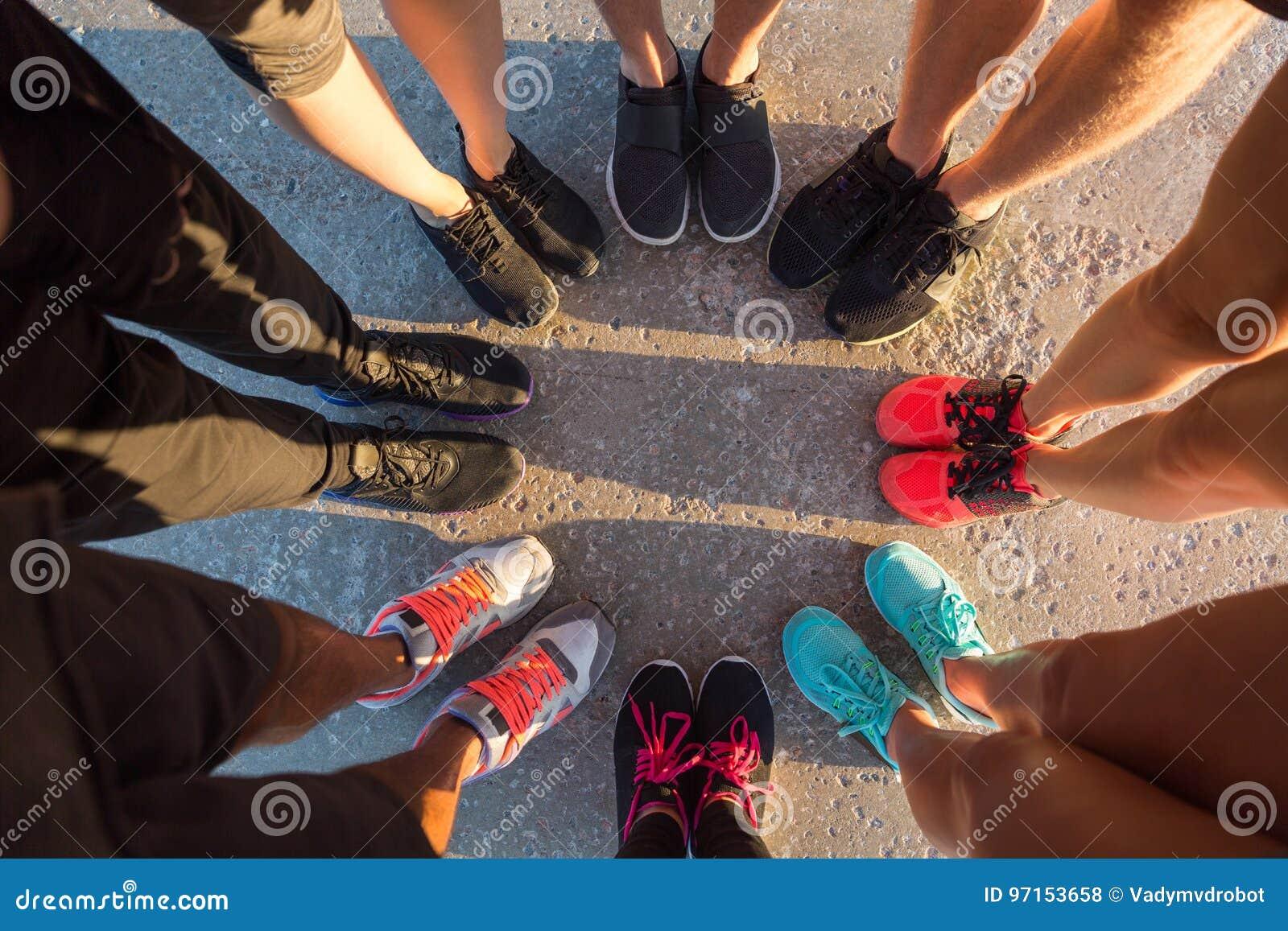 一起站立在与他们的脚的杂乱的一团的赛跑者
