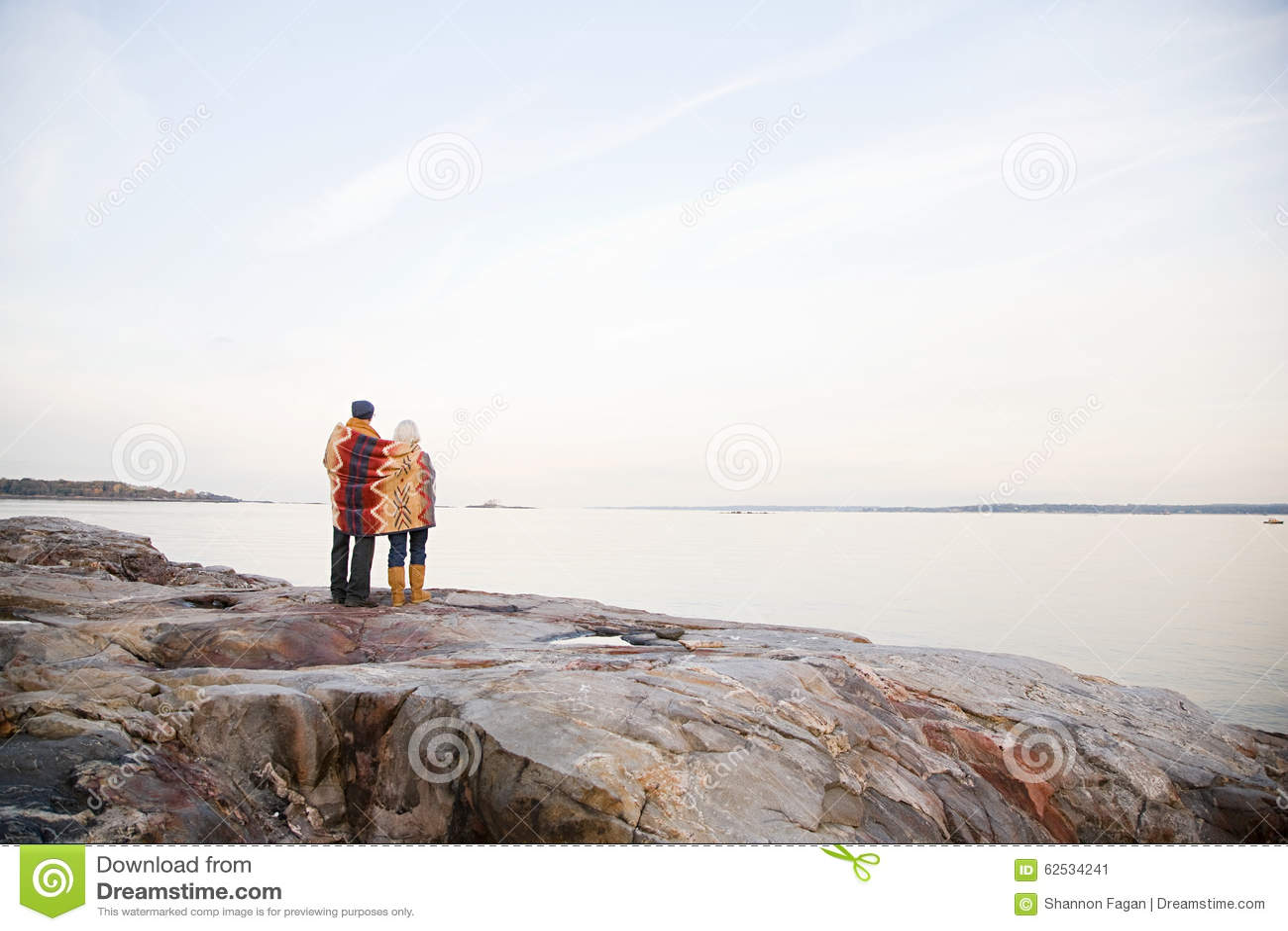 一起站立在岩石的成熟夫妇