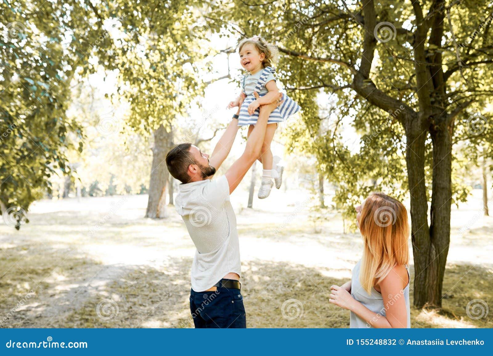 一起花费时间的愉快的年轻家庭外部在绿色自然 父母,童年,孩子,关心,女儿,父亲,母亲