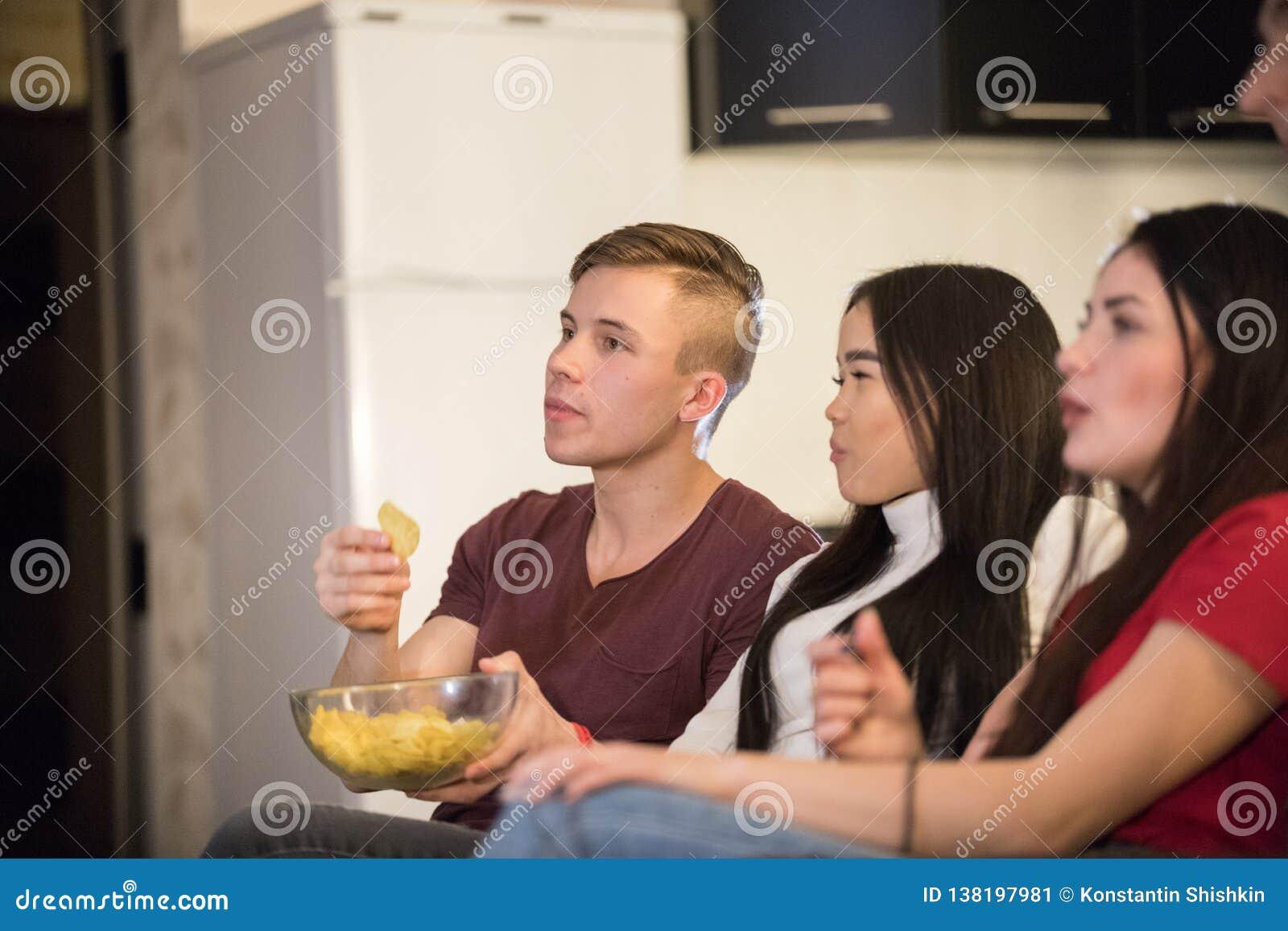 一起花费时间看着电视和吃玉米花和芯片的年轻朋友公司