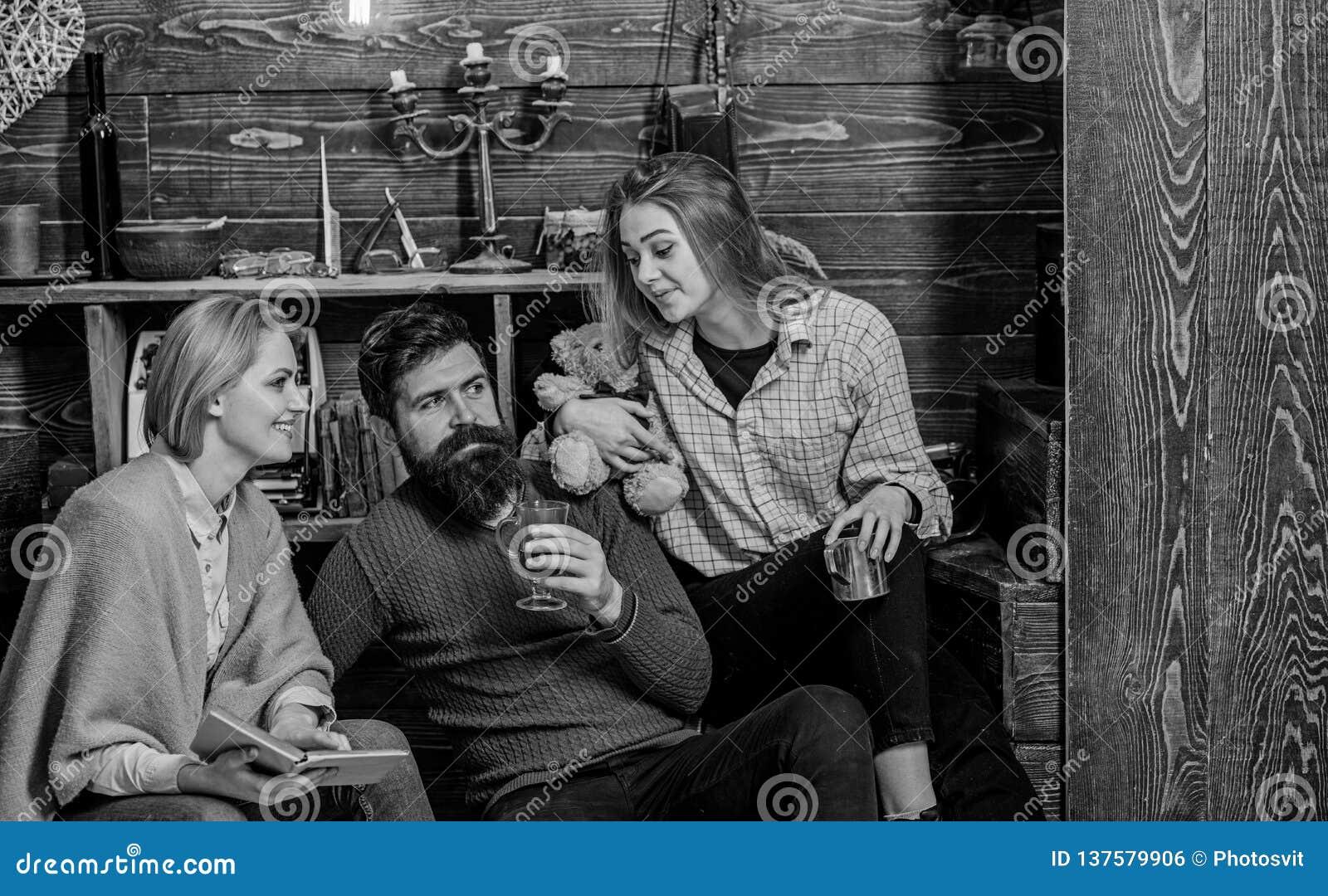 一起读在长沙发的书痴家庭  父母和十几岁的女儿消费圣诞节在乡下 博若莱红葡萄酒