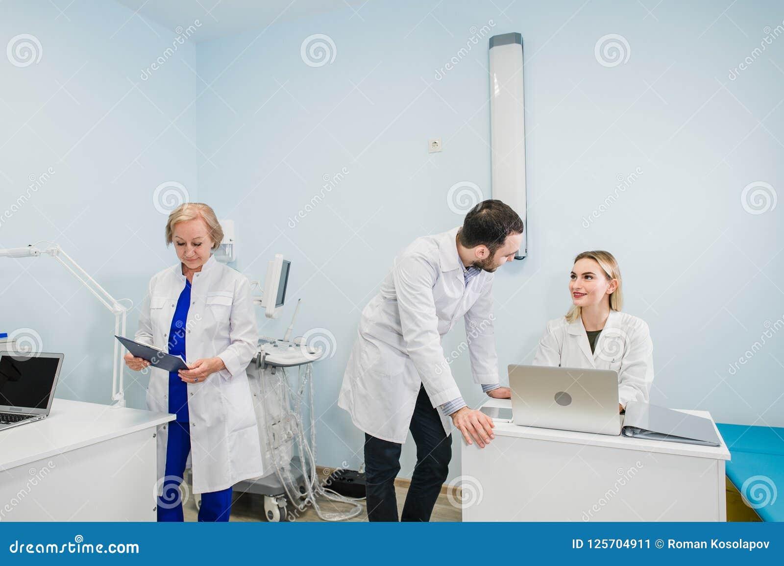 一起谈论三位的医生照片治疗新的方式,当开会议在办公室时 使用膝上型计算机的医生