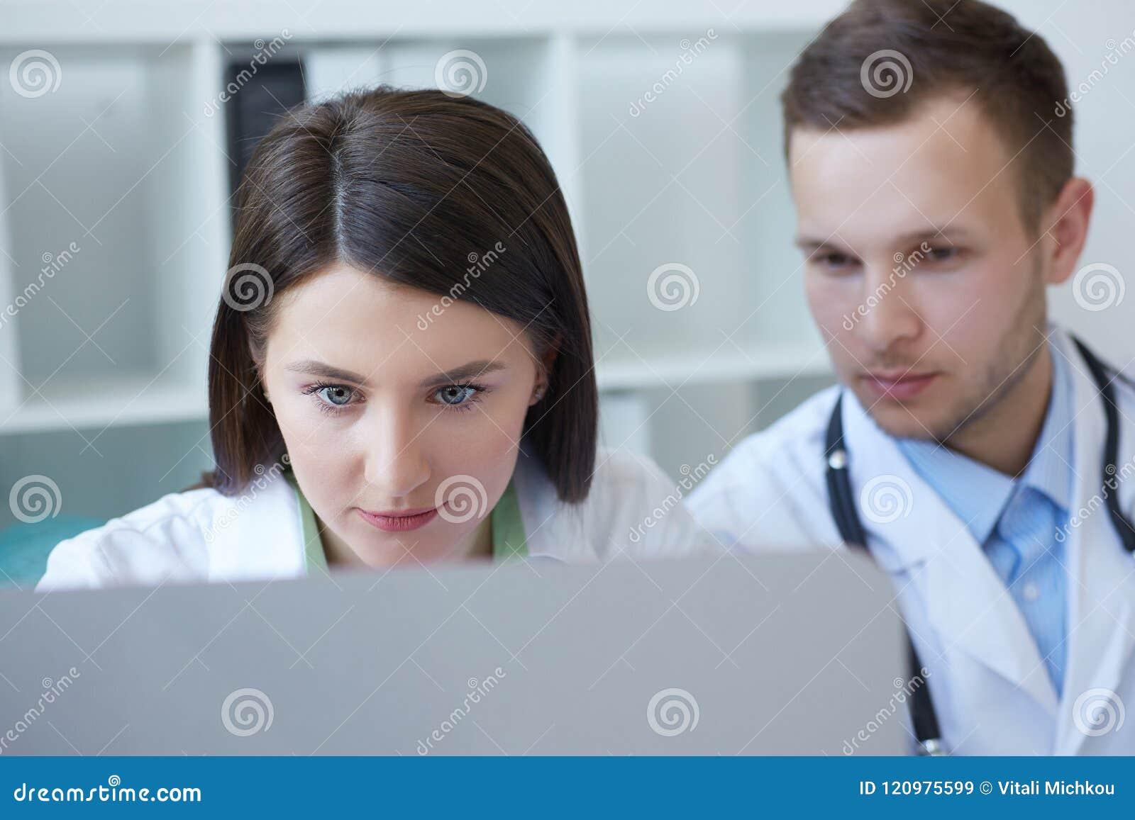 一起谈论两位年轻的医生治疗新的方式,当开会议在办公室时 使用桌面的医生