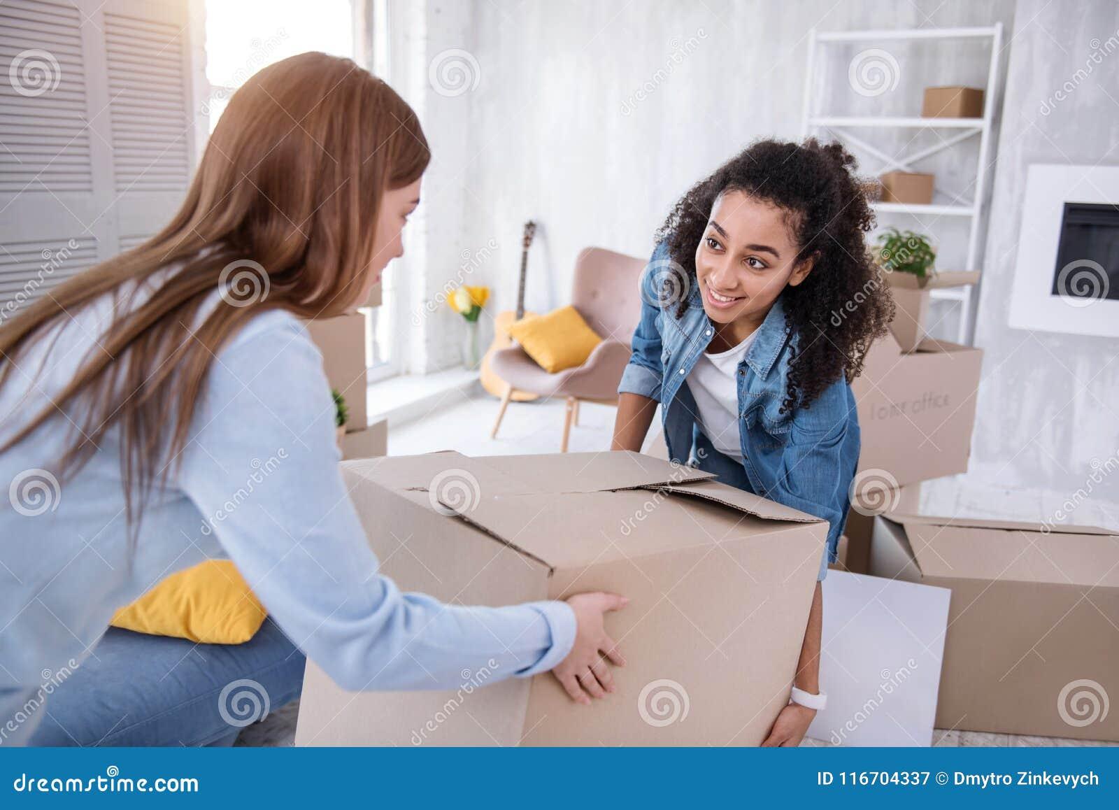 一起运载重的箱子的快乐的女孩