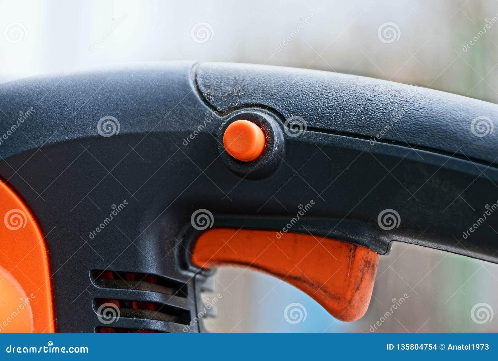 一部分的有橙色按钮的一套电动工具和在黑塑料把柄的一台触发器