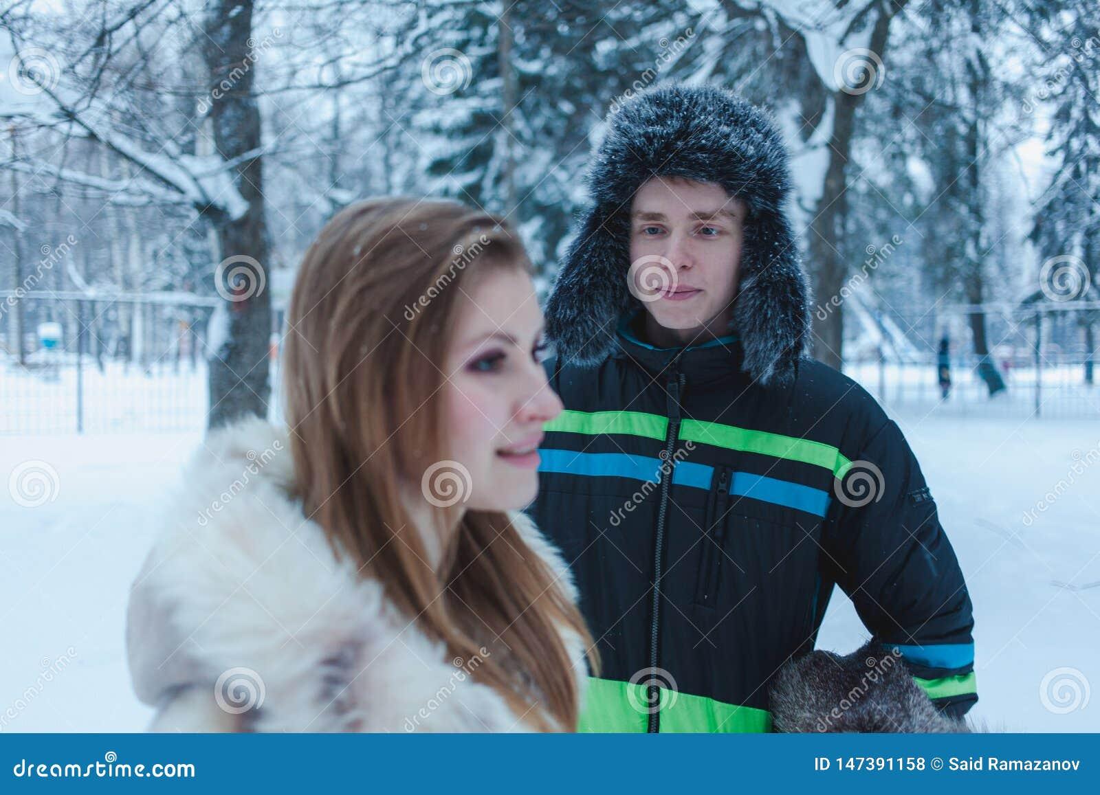 一顶裘皮帽有earflap的和一个女孩的年轻人以冬天森林为背景的一米黄毛皮大衣的