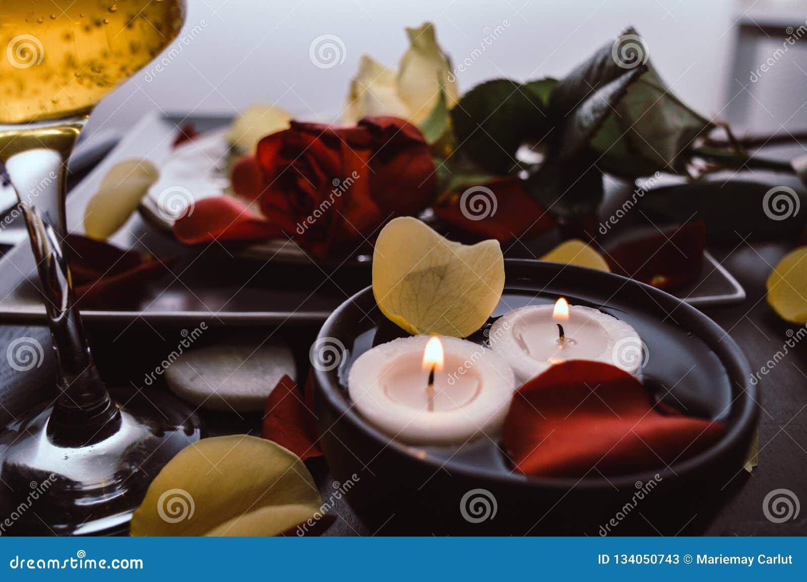 一顿美好的浪漫晚餐的特写镜头与香槟玻璃泡影,花瓣,玫瑰,蜡烛的 日s华伦泰