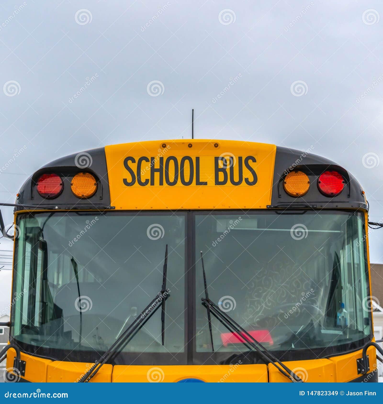 一黄色学校班车和多云天空的清楚的方形的正面图有家的在背景中