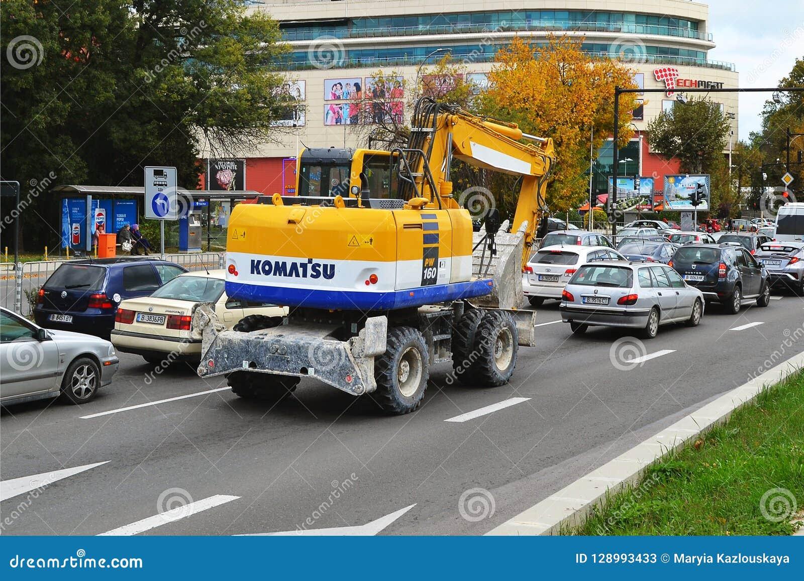 一黄色挖掘机或buldozer与weels在一条城市街道上在汽车中在一天