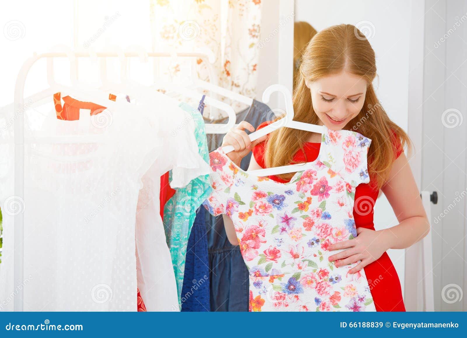 一件红色礼服的妇女在镜子看并且选择衣裳