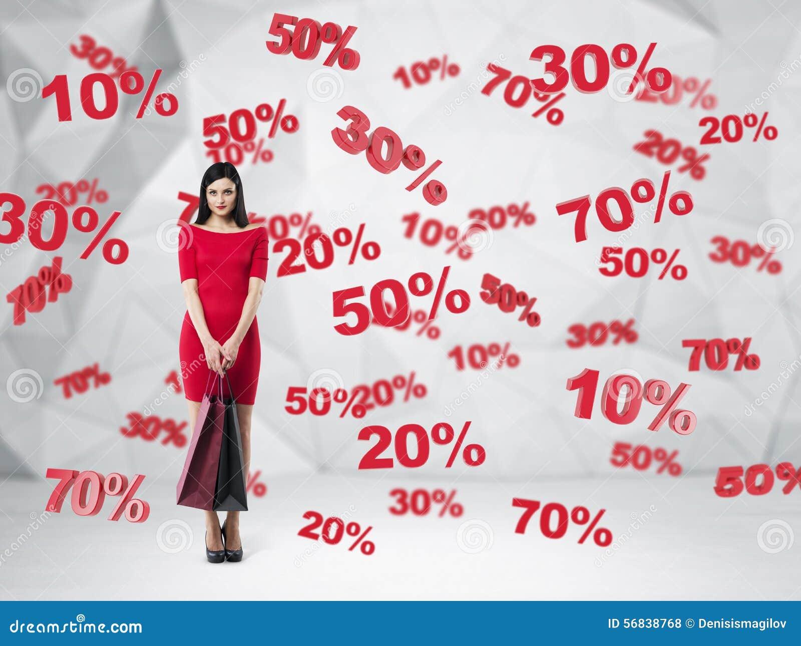 一件红色礼服的浅黑肤色的男人有购物袋的 折扣和销售标志:10  20  30  50  70  当代背景