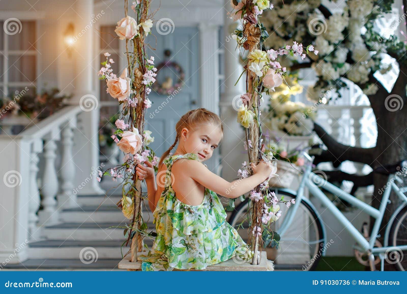 一件绿色礼服的逗人喜爱的小女孩坐摇摆装饰了wi