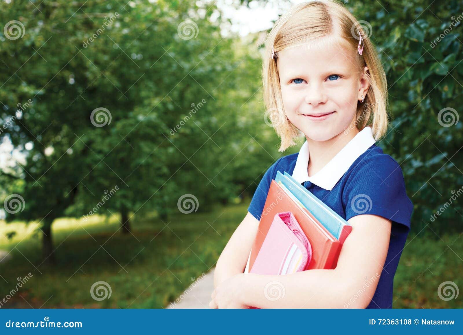 一件蓝色学校礼服的微笑的女小学生,有bo的