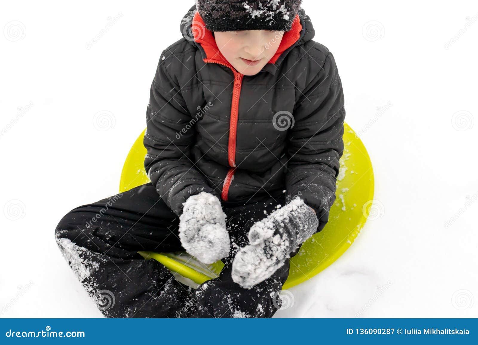七岁的男孩坐准备好一个绿色塑料茶碟的雪撬乘坐幻灯片 冬天活动的概念,休闲