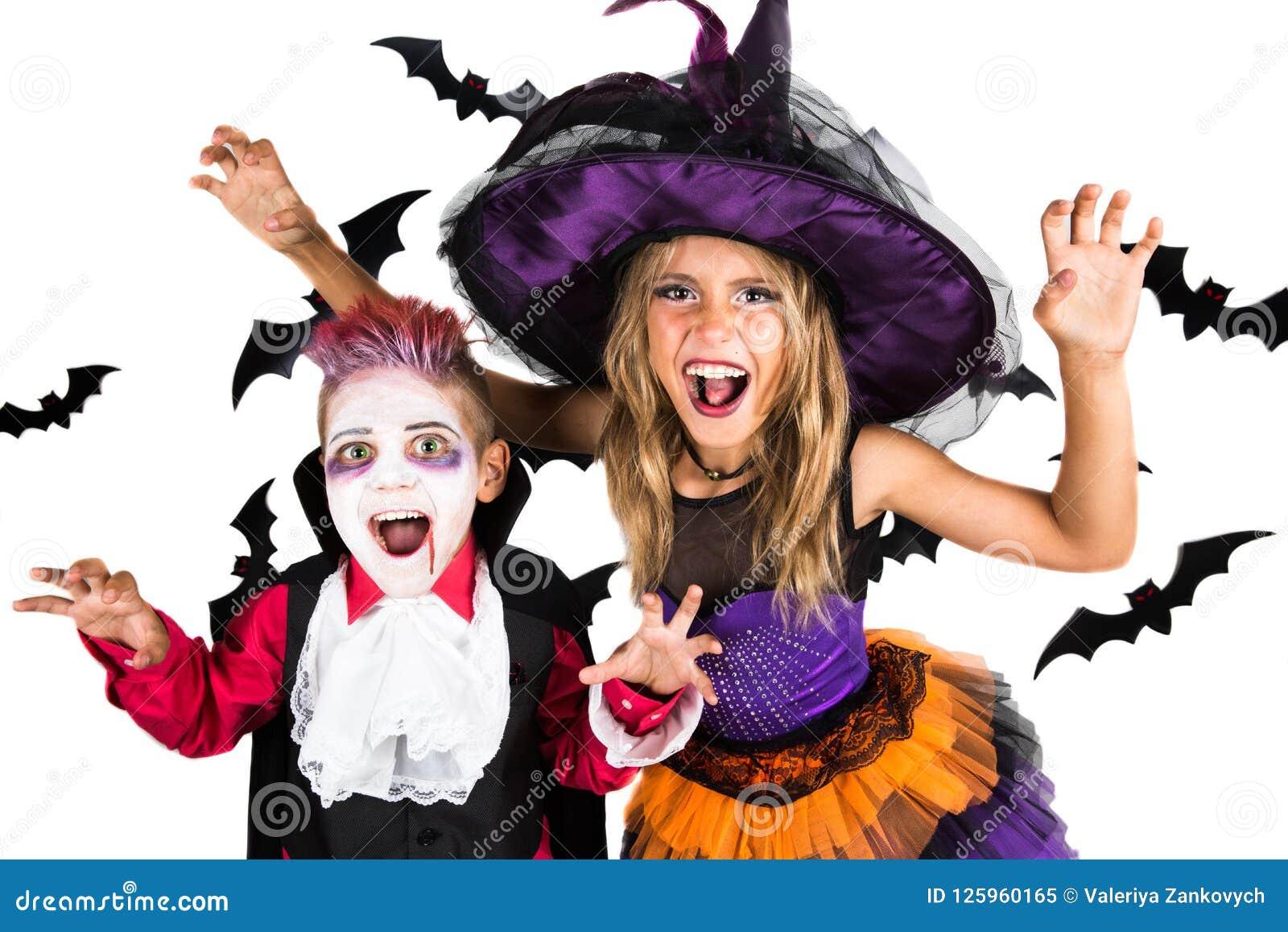 万圣夜孩子、愉快的可怕女孩和男孩在巫婆、巫师和吸血鬼南瓜补丁的德雷库拉万圣夜服装装饰了