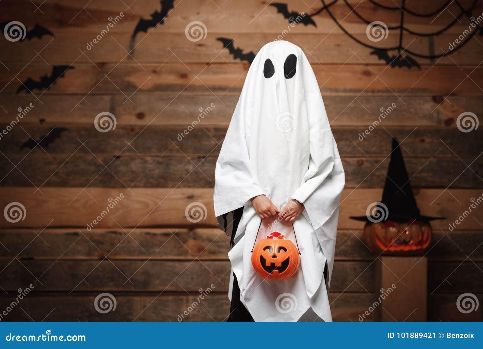 万圣夜概念-与万圣夜南瓜做把戏或款待用弯曲的南瓜的糖果瓶子的一点白色鬼魂在棒和sp