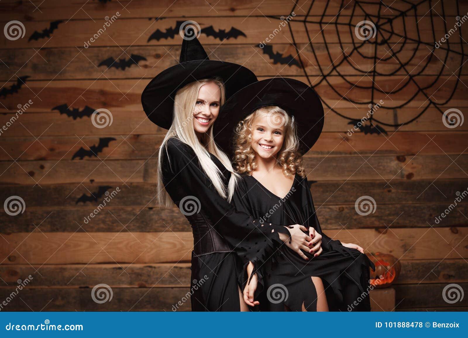 万圣夜概念-快乐的巫婆服装的庆祝万圣夜的母亲和她的女儿摆在用弯曲的南瓜在棒