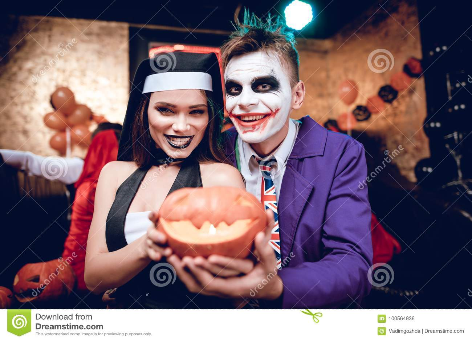 万圣节当事人 说笑话者服装的一个人和尼姑的一个女孩打扮摆在与南瓜灯