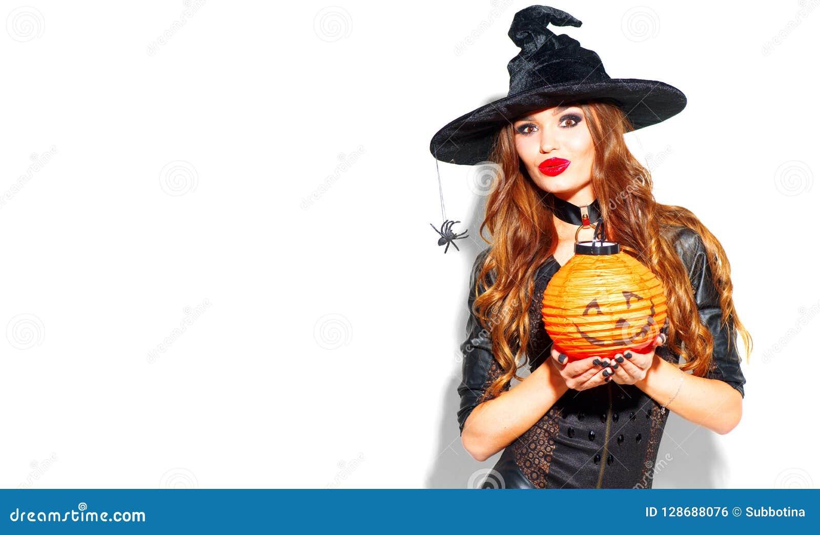 万圣节 有明亮的假日构成的性感的巫婆 摆在有南瓜灯笼的巫婆服装的美丽的少妇