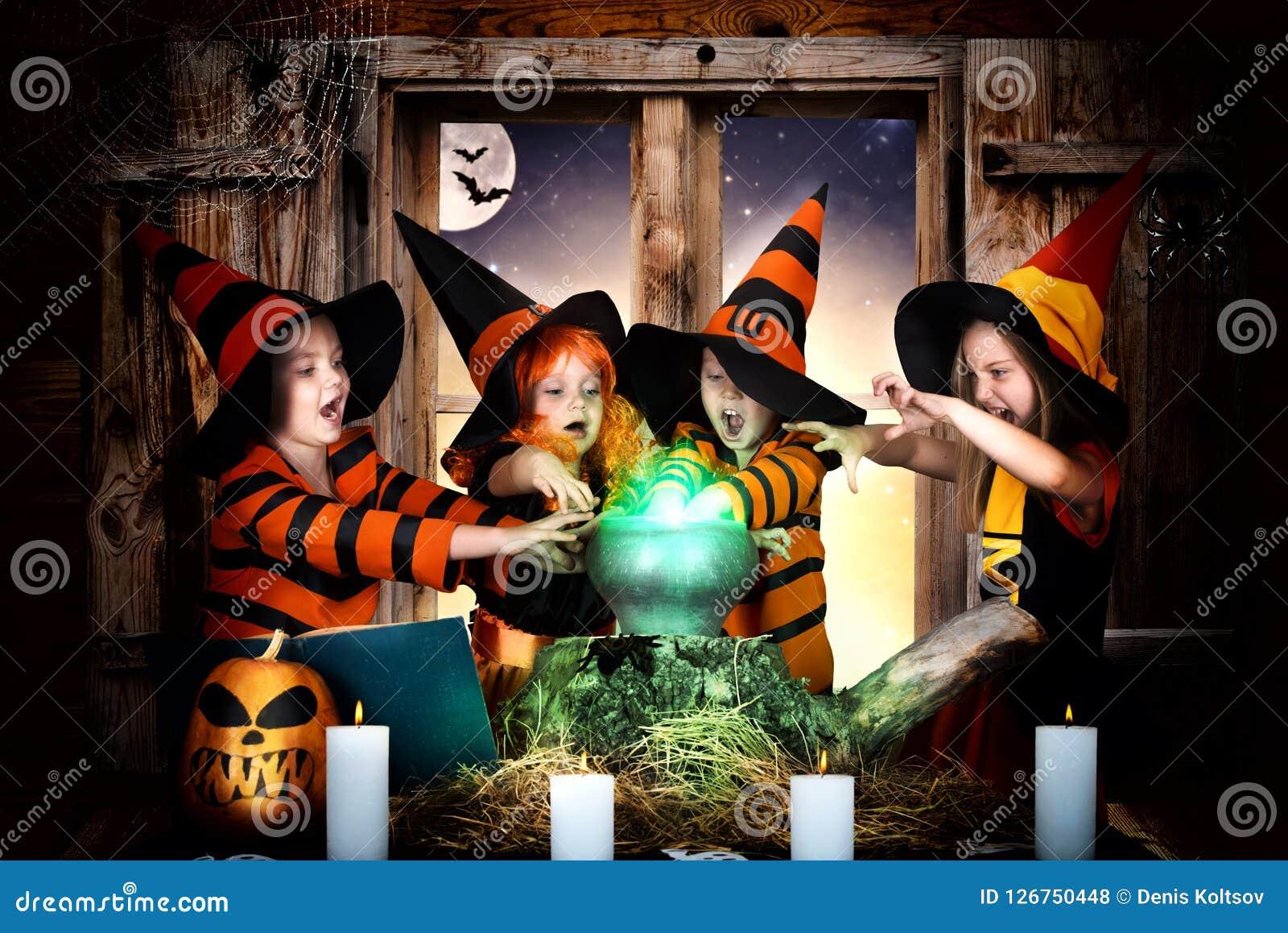 万圣节 烹调在大锅的巫婆和巫术师的孩子魔药用南瓜和咒语书