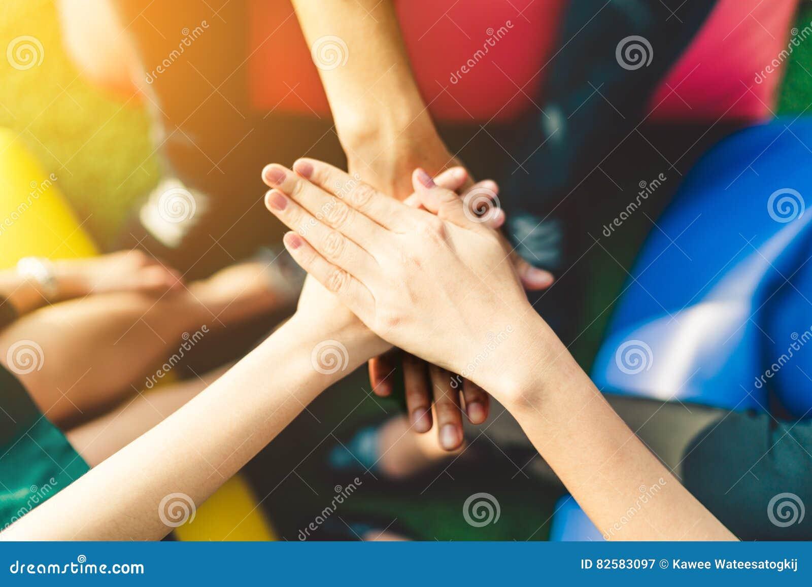 三只年轻商人加入的手合作,配合或者团结概念