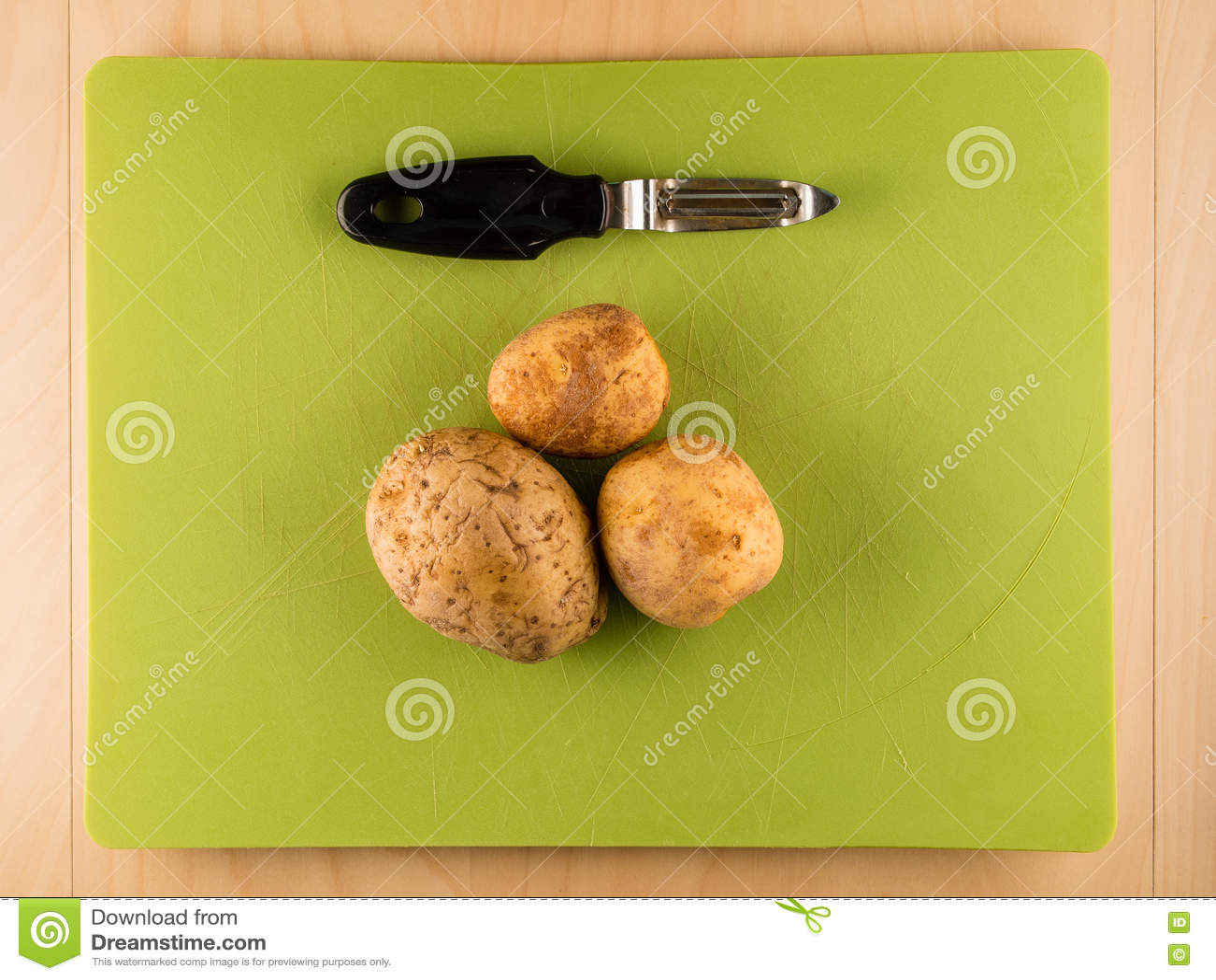 三台土豆和削皮器在绿色塑料委员会