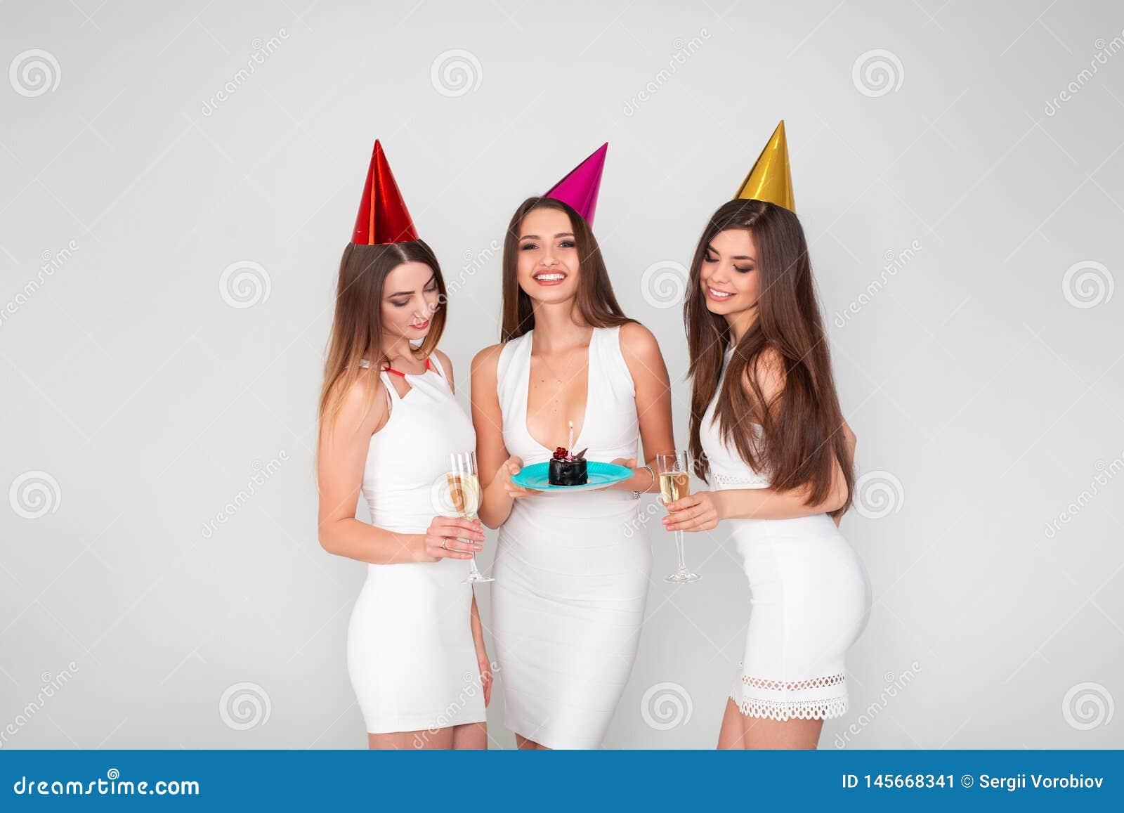 三名美丽的端庄的妇女庆祝节日晚会,获得与蛋糕的乐趣和喝鸡尾酒和香槟