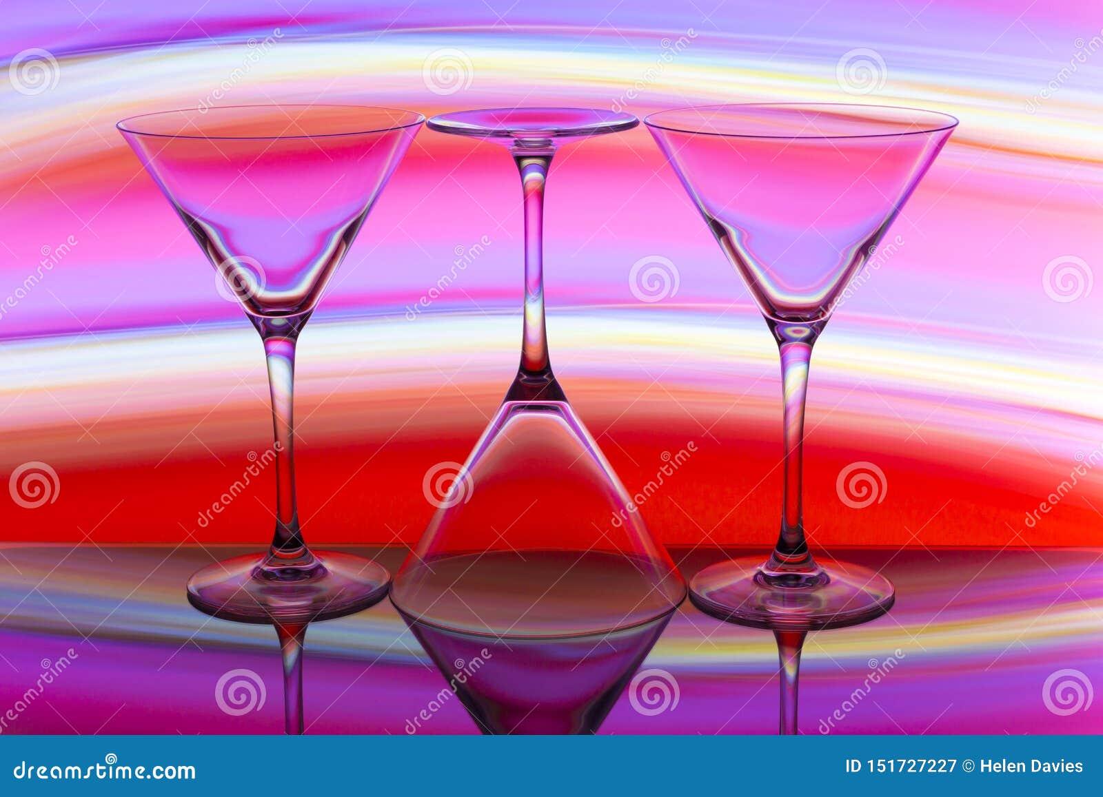 三块鸡尾酒/马蒂尼鸡尾酒玻璃连续与颜色彩虹在他们后