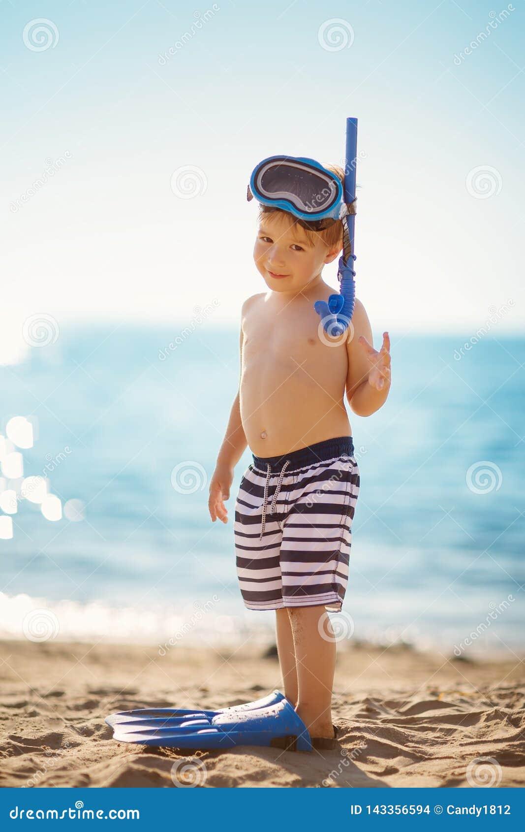 三岁使用在与游泳圆环的海滩的男孩