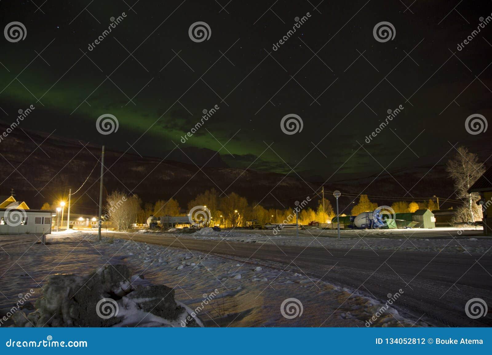 上升在一座山后的北极光极光borealis在挪威的北部的一个小村庄 冬天中