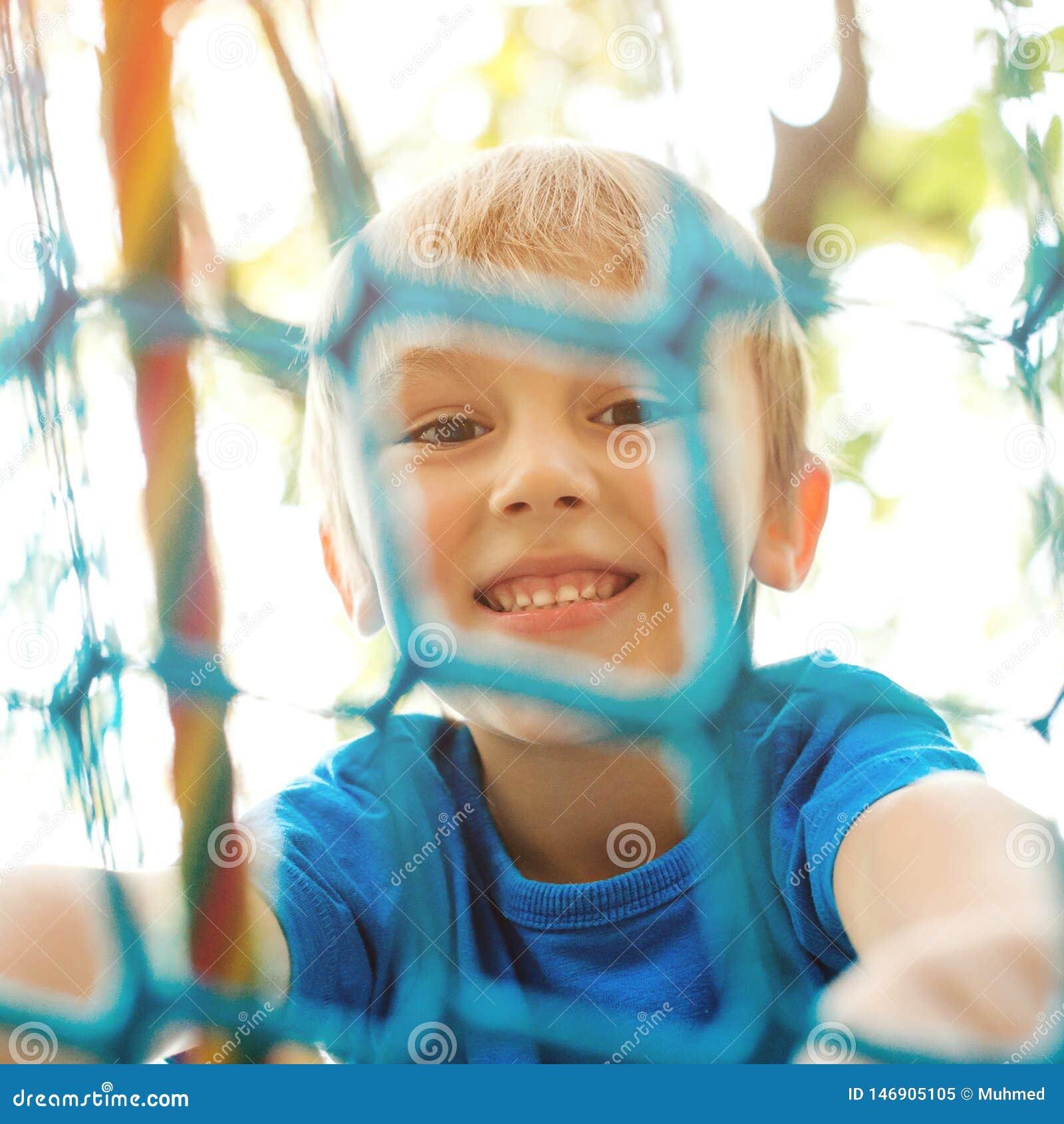 上升在操场绳索的愉快的孩子 使用在现代操场的快乐的小男孩 微笑的孩子获得乐趣在冒险
