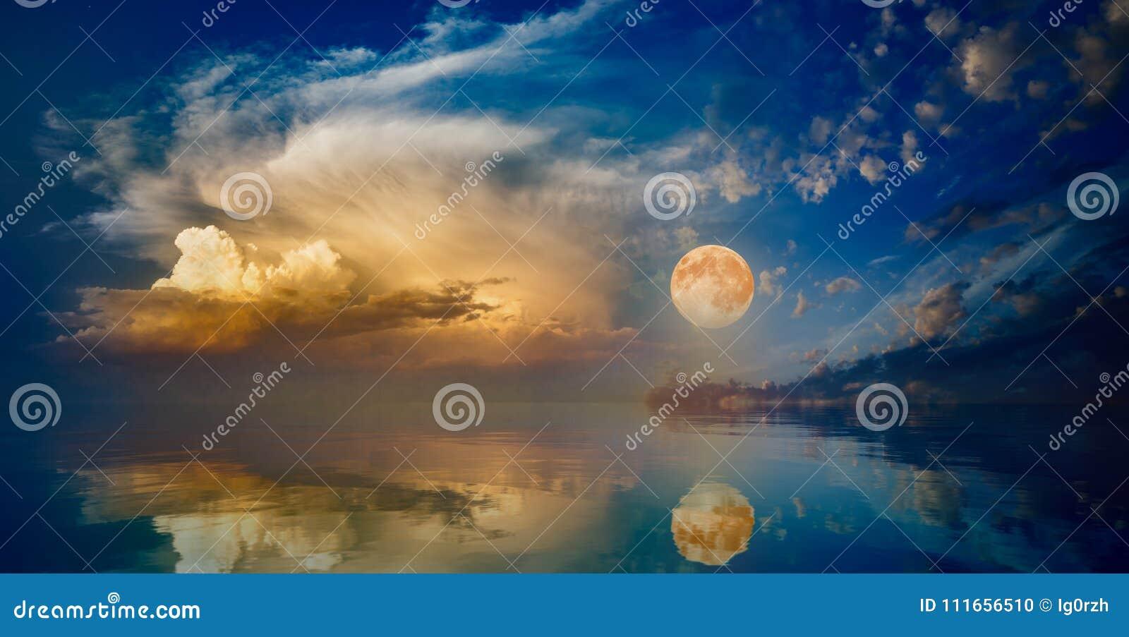 上升在日落天空的平静的海上的满月