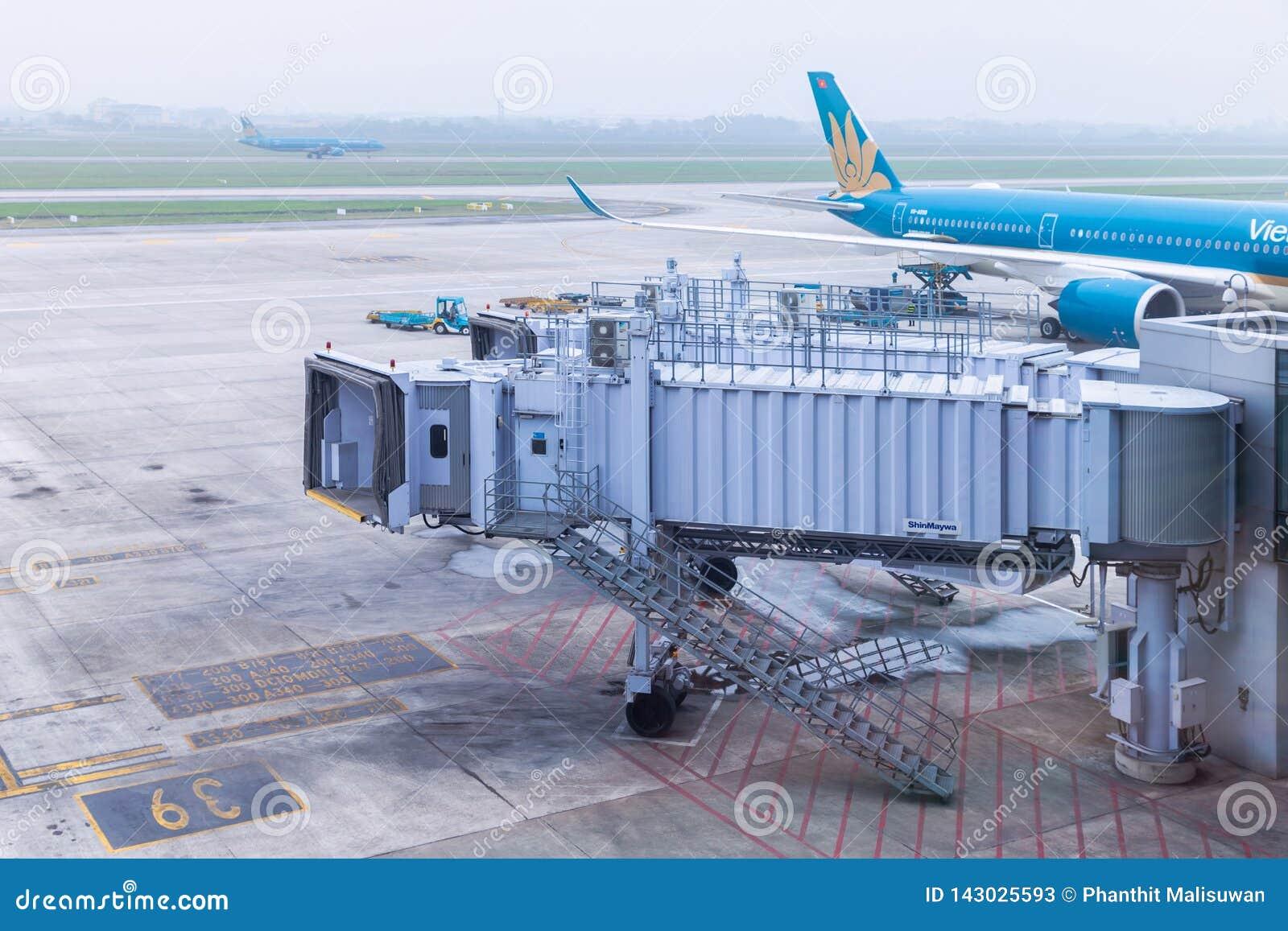 上的桥梁或喷气机桥梁由地面服务乘员组为乘客做准备离去或抵达Noi Bai国际机场