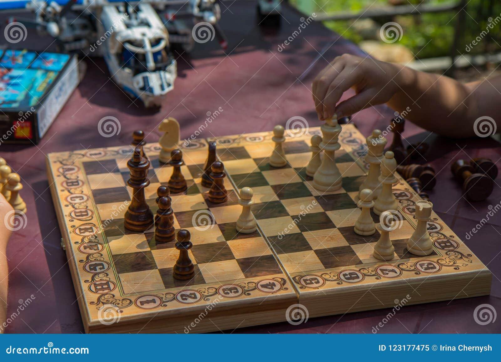 下棋的孩子在有被弄脏的玩具的庭院里在背景