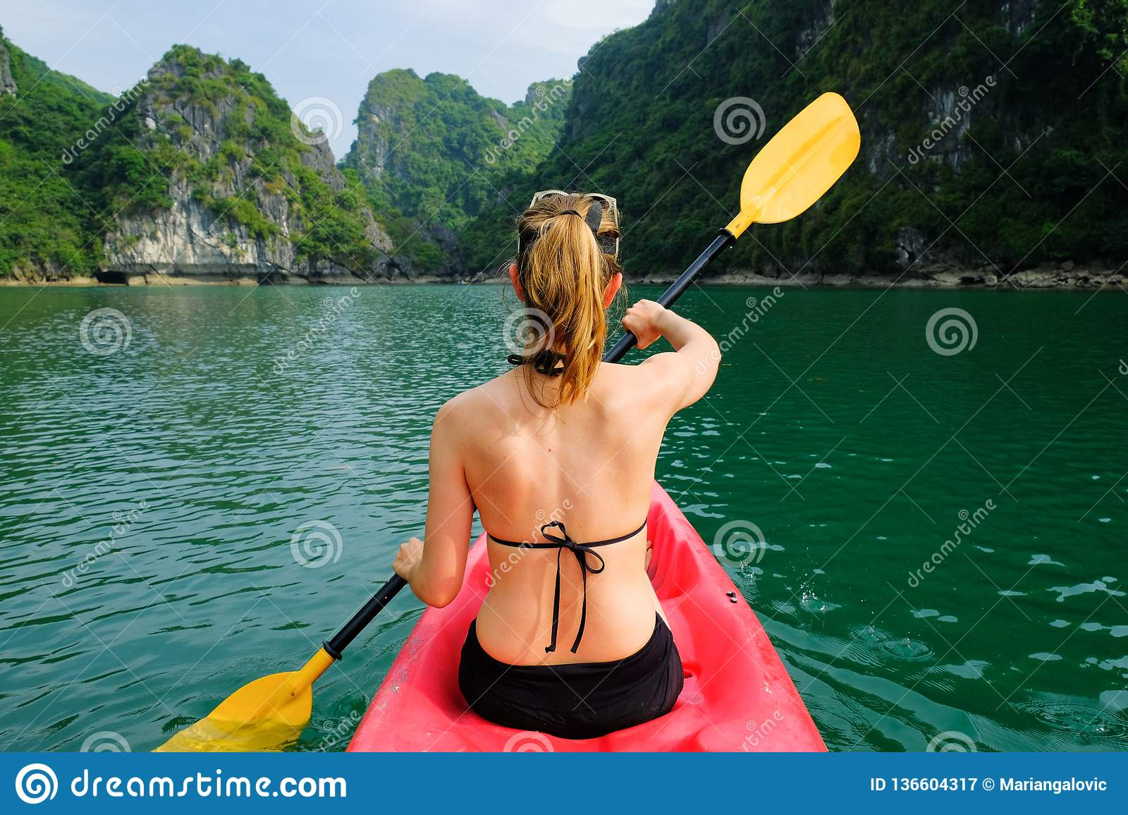 下龙湾/越南,06/11/2017:皮船的妇女用浆划通过石灰岩地区常见的地形海岛和密集的密林的在下龙湾/猫Ba海岛