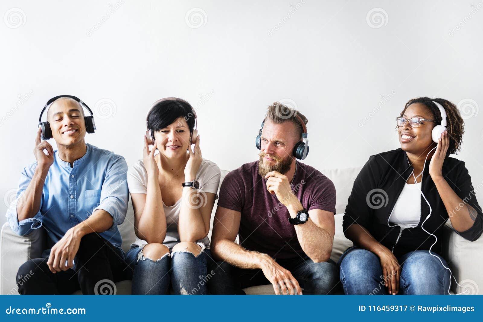 不同的人民坐长沙发佩带的耳机