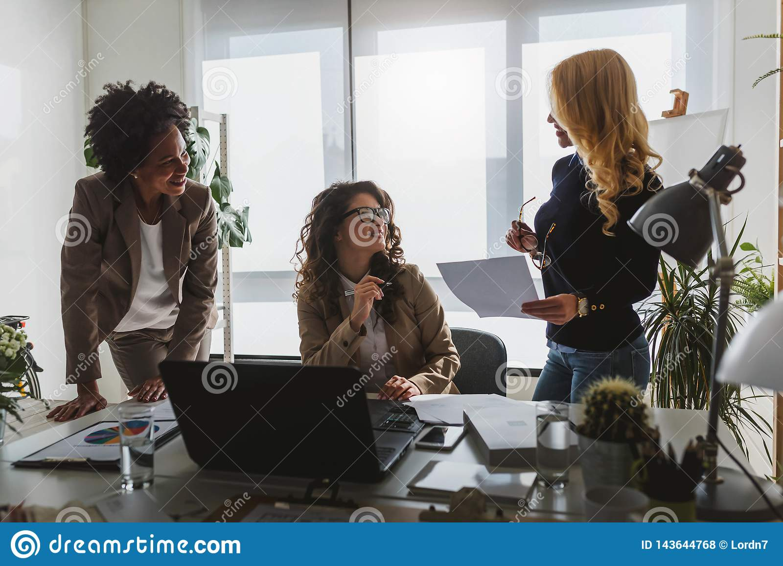 不同的小组微笑的女商人有断裂在办公室谈话