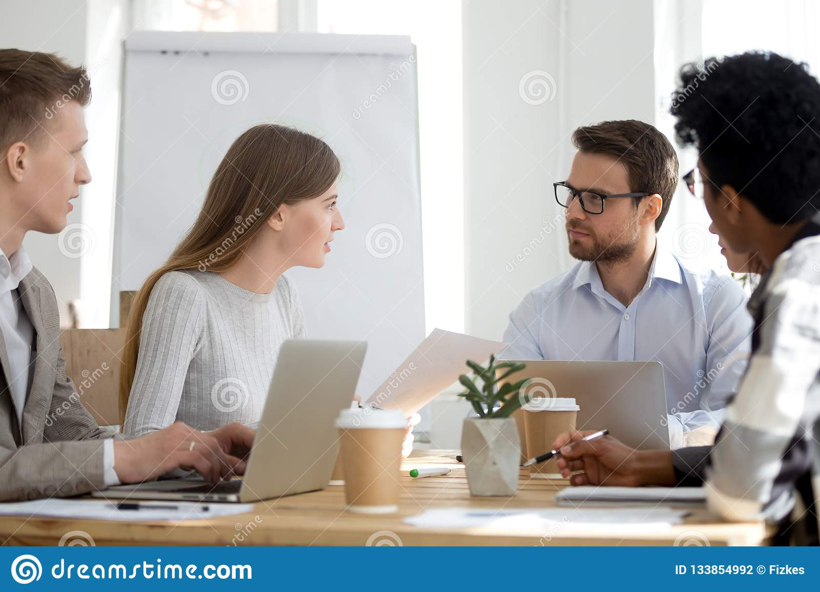 不同的雇员坐在遇见合作在办公室