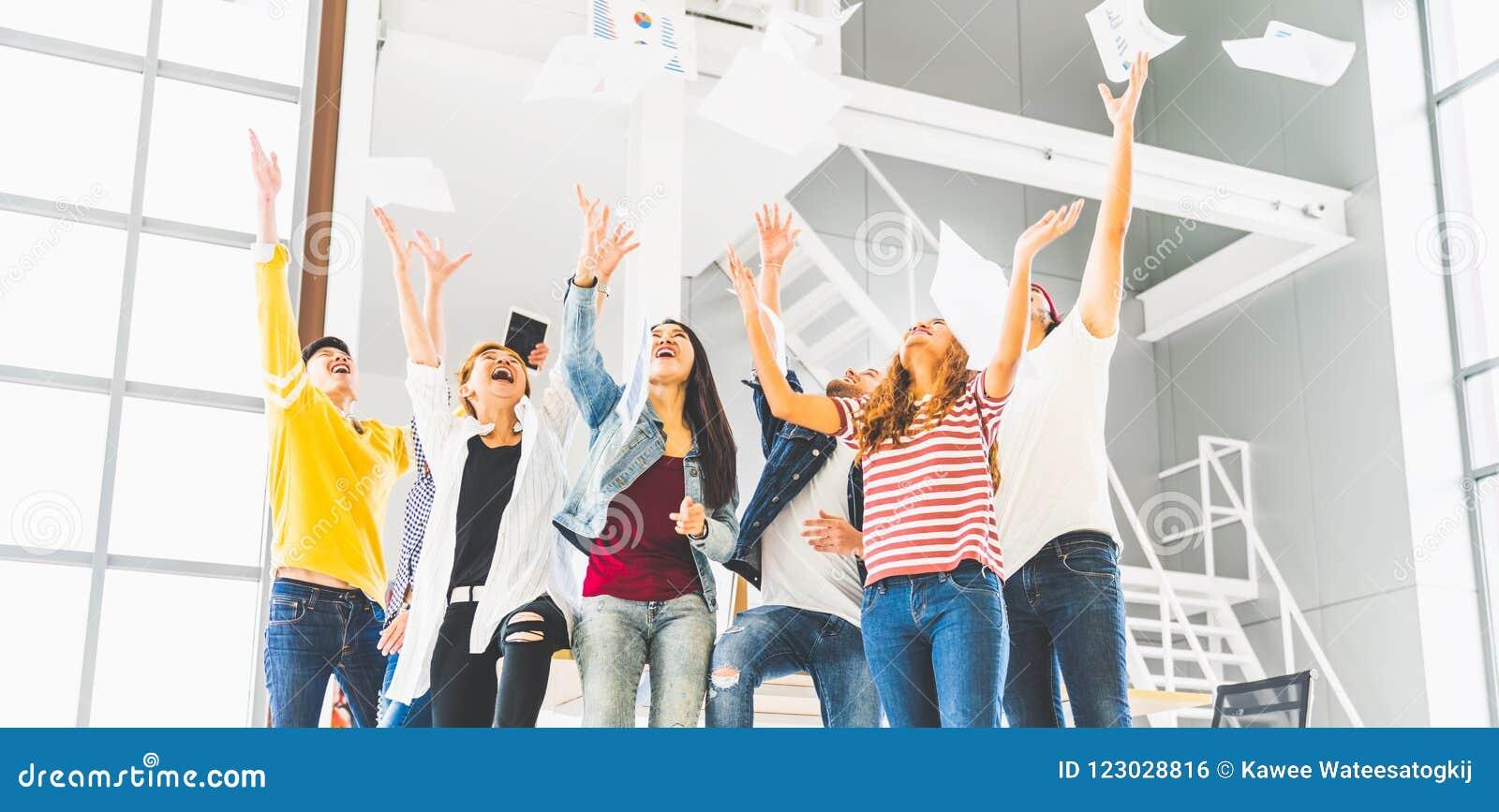 不同种族的不同的愉快的队一起庆祝项目成功投掷纸  公司社区或者小企业概念