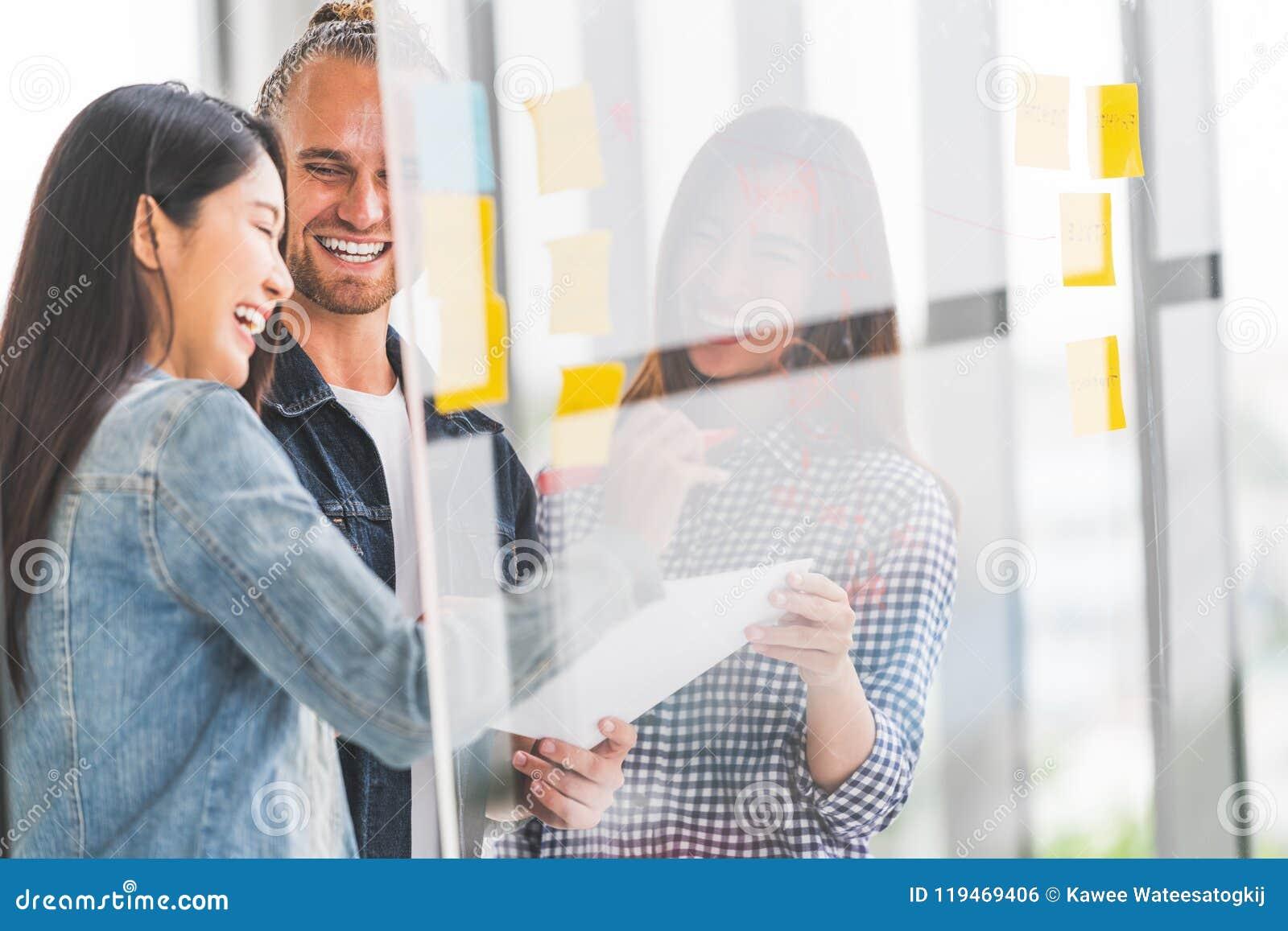 不同种族的不同的队会议在透明玻璃,柱子贴纸,坦率的微笑一起写项目目标计划