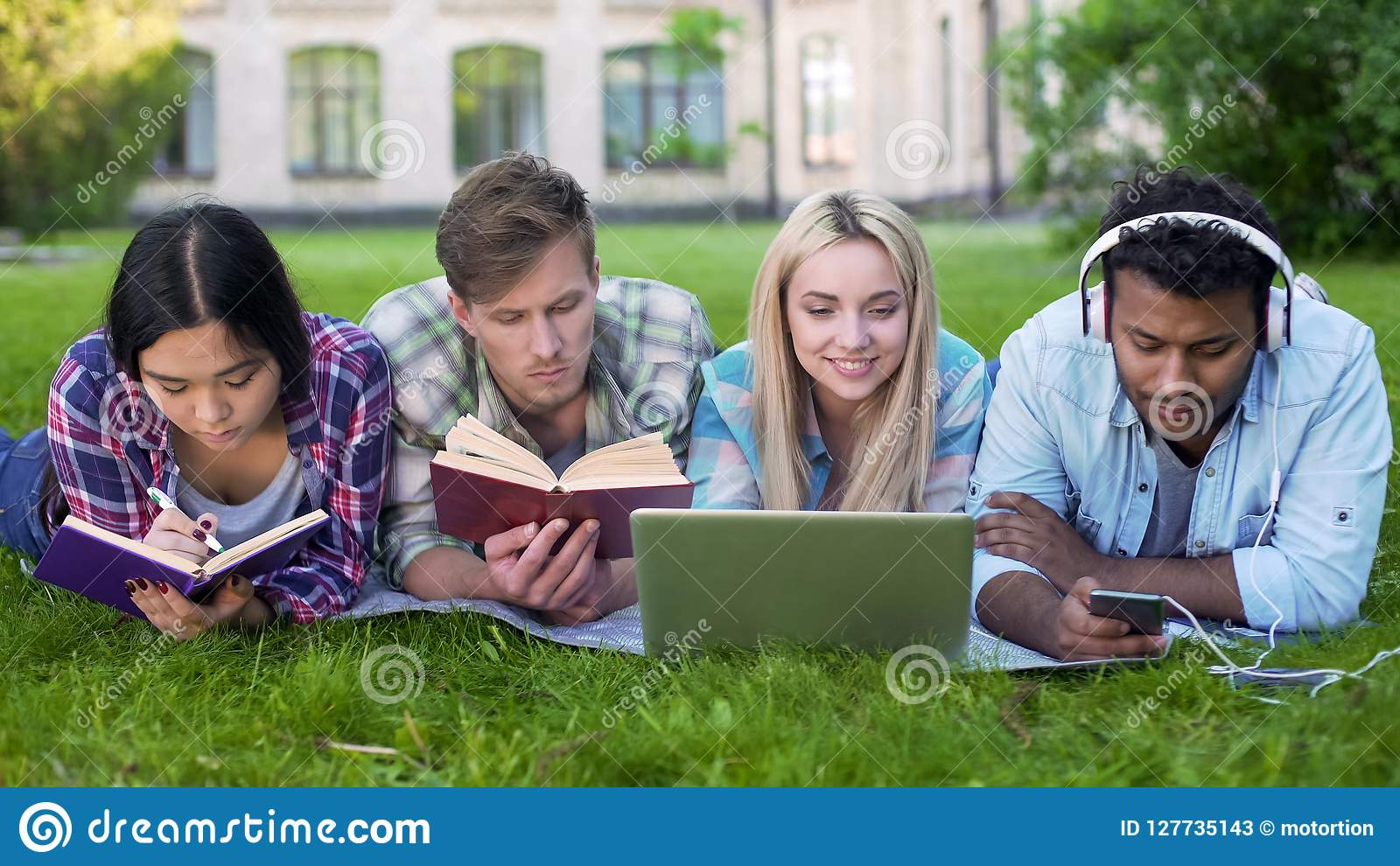 不同种族的做在草的男人和妇女家庭作业在校园里,高等教育