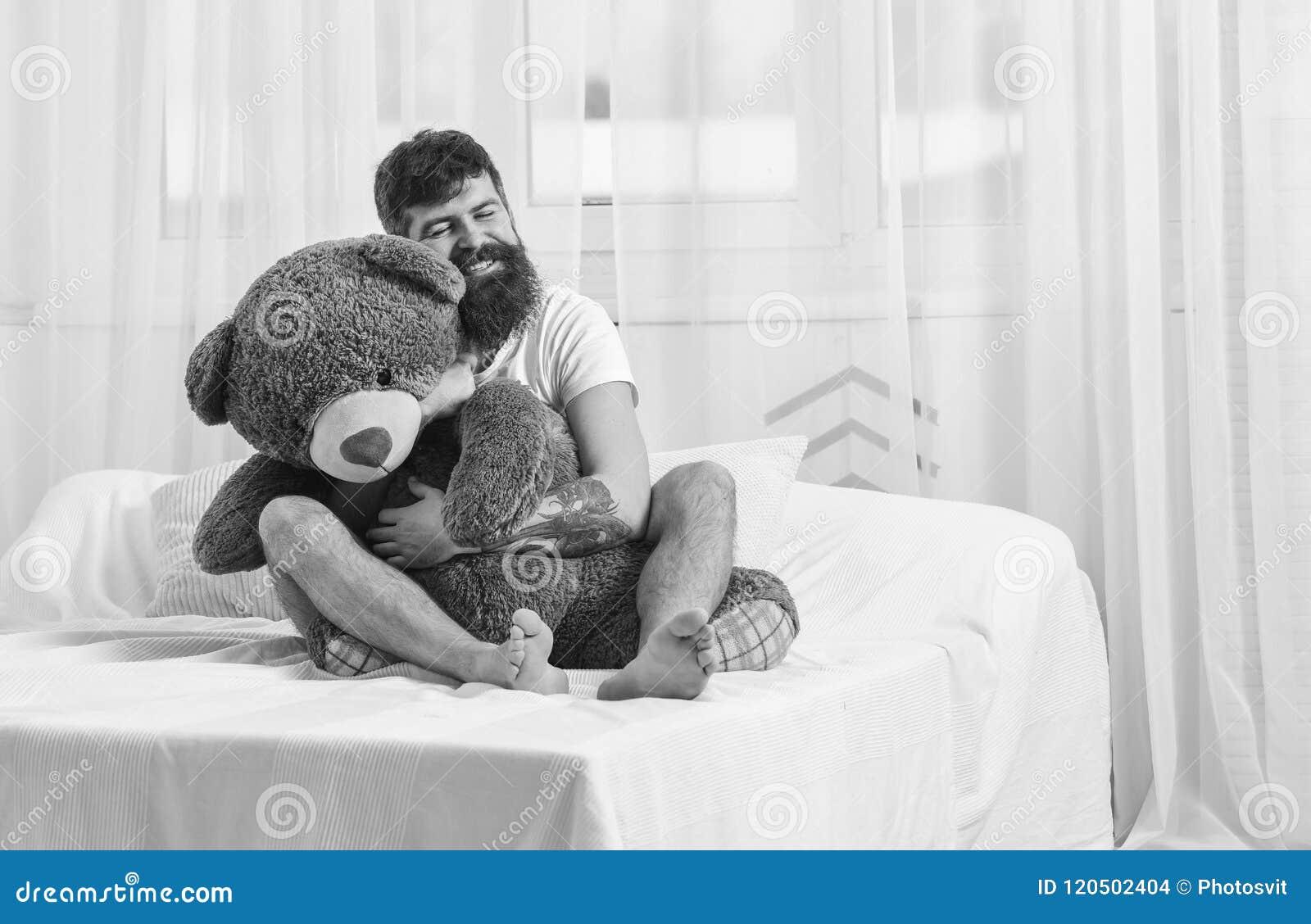 不要长大概念 愉快的面孔的人拥抱巨型玩具熊 人坐床并且拥抱大玩具,白色帷幕
