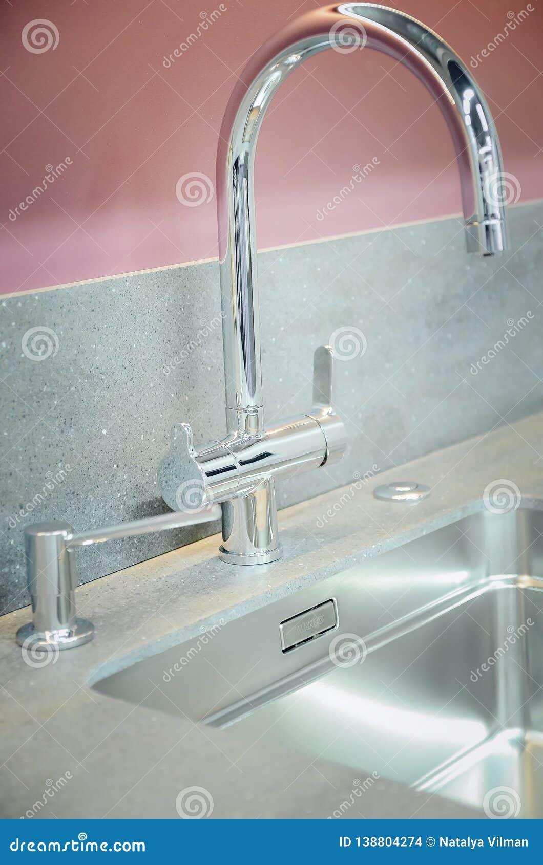 与一个人为石工作台面的一个新的厨房水槽 现代厨房内部的概念 垂直的摄影 特写镜头,